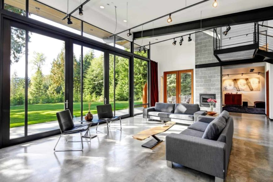The expansive living room showcases a panoramic window overlooking the lush green outdoor view. It has concrete flooring and a white ceiling mounted with hanging track lights.