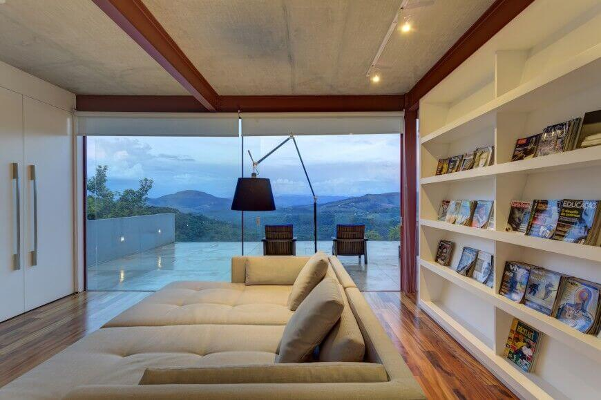 This modern living room showcases built-in shelving and a beige tufted sofa illuminated by an ambient floor lamp. It includes hardwood flooring and a full-height window overlooking the stunning mountains.