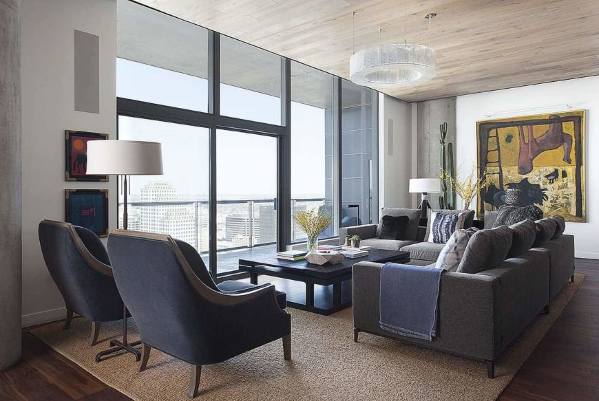 Industrial living room with tinted glass windows, gray seats paired with a dark wood coffee table and white walls adorned by gorgeous artworks. It is illuminated by a round chandelier that hung from the wood plank ceiling.