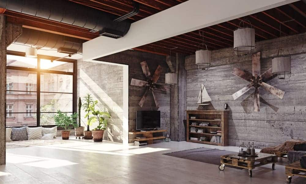 Industrial living room incorporated with a rustic style. It has distressed wood-paneled walls and floor to ceiling windows bringing plenty of natural light in.