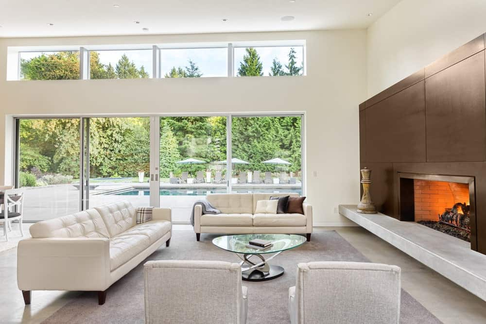 Living room furnished with matching white tufted sofas and gray armchairs along with a glass top coffee table that sits on a gray area rug. It features large glazed windows overlooking the sparkling poo and surrounding greenery.