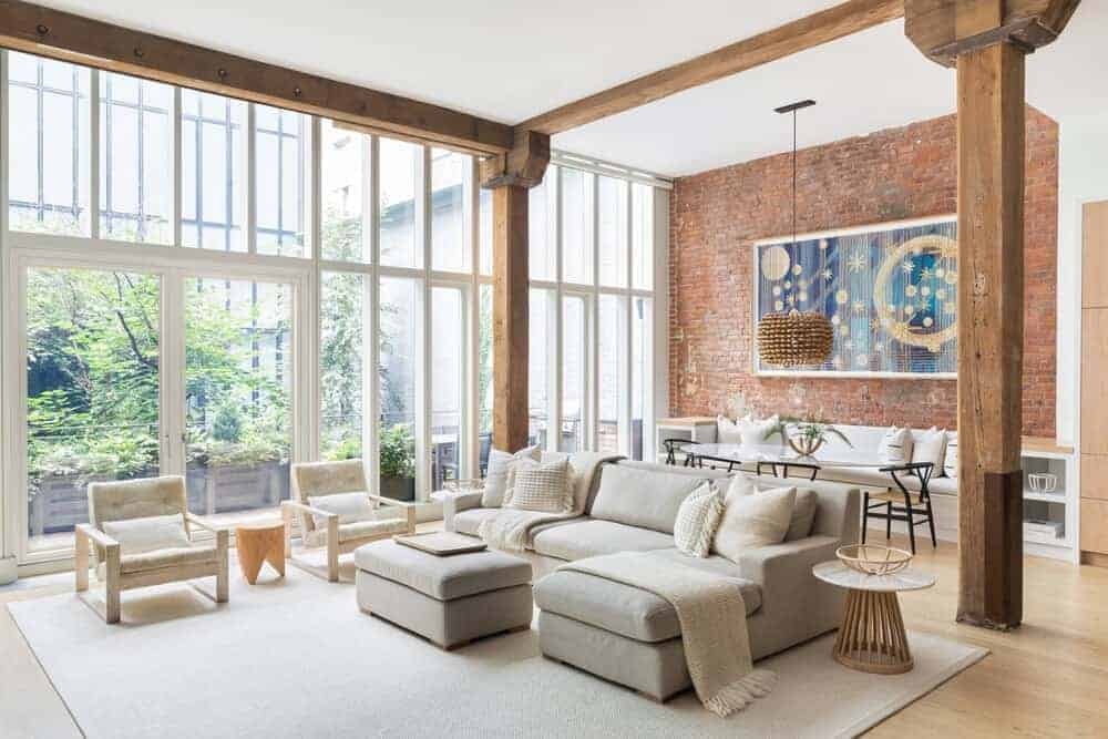 Light and airy living room with comfy seats and round side tables over a large area rug. It has exposed wood beams and columns along with full height windows that let plenty of natural light in.