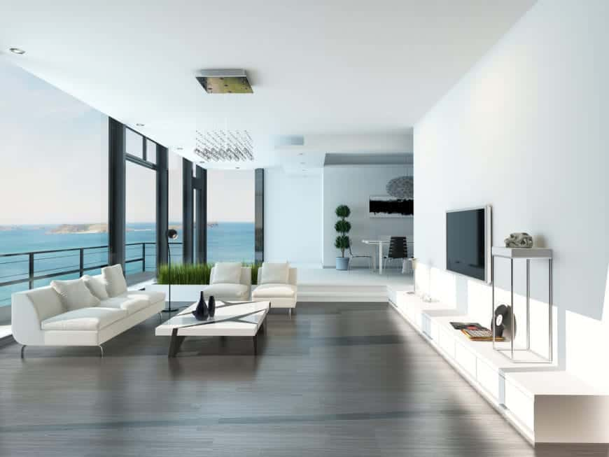 Minimalist living room with full height glazing overlooking the stunning ocean view. It is illuminated by a raindrop chandelier that hung over a white coffee table surrounded by white sofa and chairs.