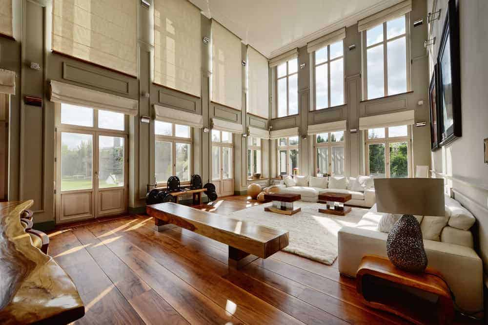 A large living room featuring a stylish bench seating, two large sofa sets and classy center tables set on the rug covering the hardwood flooring. It is surrounded by gray walls and plenty of large windows covered in translucent shades.