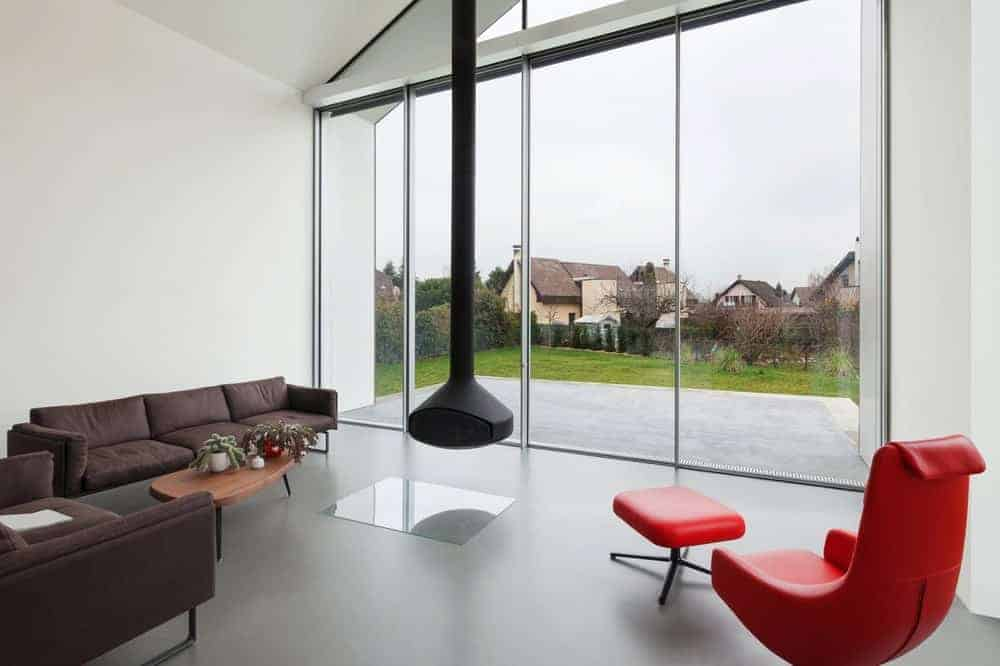 White living offers a modern hanging fireplace surrounded by brown sectional and armchair along with a red recliner and ottoman. It has concrete flooring and full height glazing that creates a sense of virtual space.