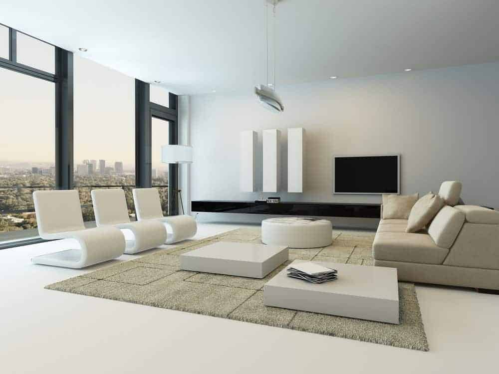 Sleek living room boasts a beige sectional facing the modern chairs with coffee tables and an ottoman in between. The room has pristine white flooring and glazed windows framing an expansive view.