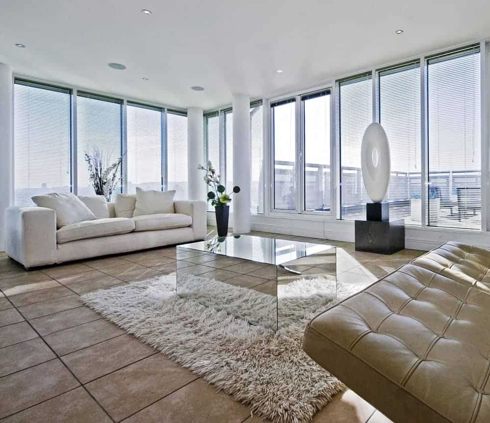 This living room features amirrored coffee table situated in between a white couch and a tufted leather sofa. The room is surrounded by glass-paneled windows covered with blinds.