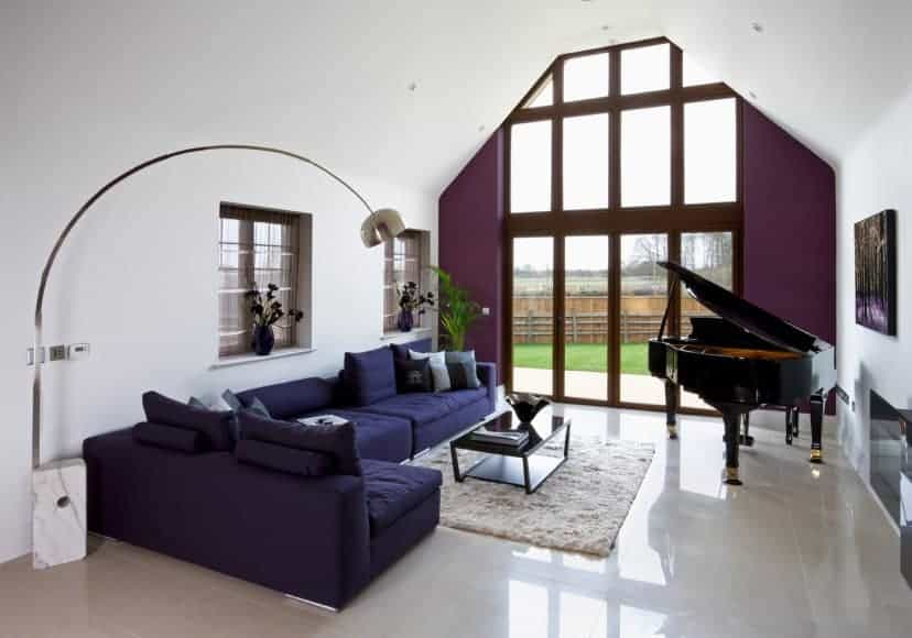 Charming living room accented with an indigo tufted sectional and a violet wall fitted with glass panels. There's a baby grand piano placed under a lovely artwork.
