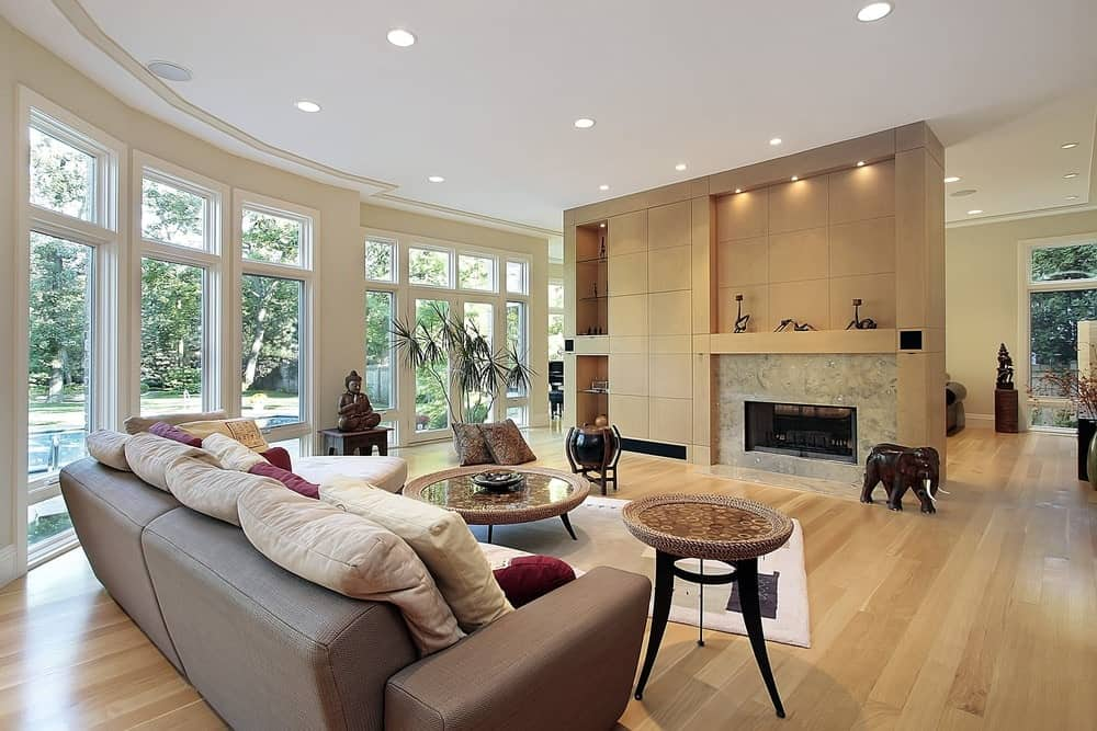A spacious living space featuring a cozy sofa set with stylish side and center tables. The area also includes a fireplace along with built-in shelving.
