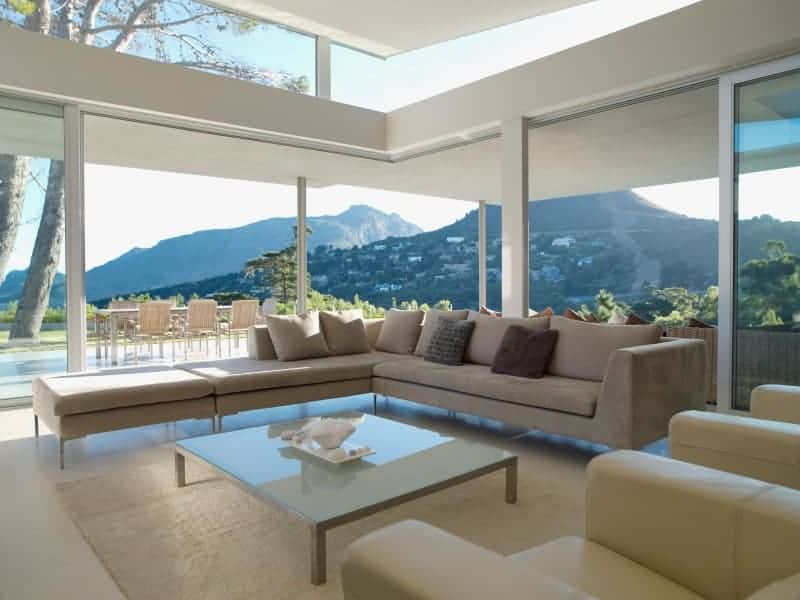 This living room boasts a panoramic window overlooking a spectacular mountain view. It is furnished with a beige velvet sectional and a glass top coffee table over a large area rug.