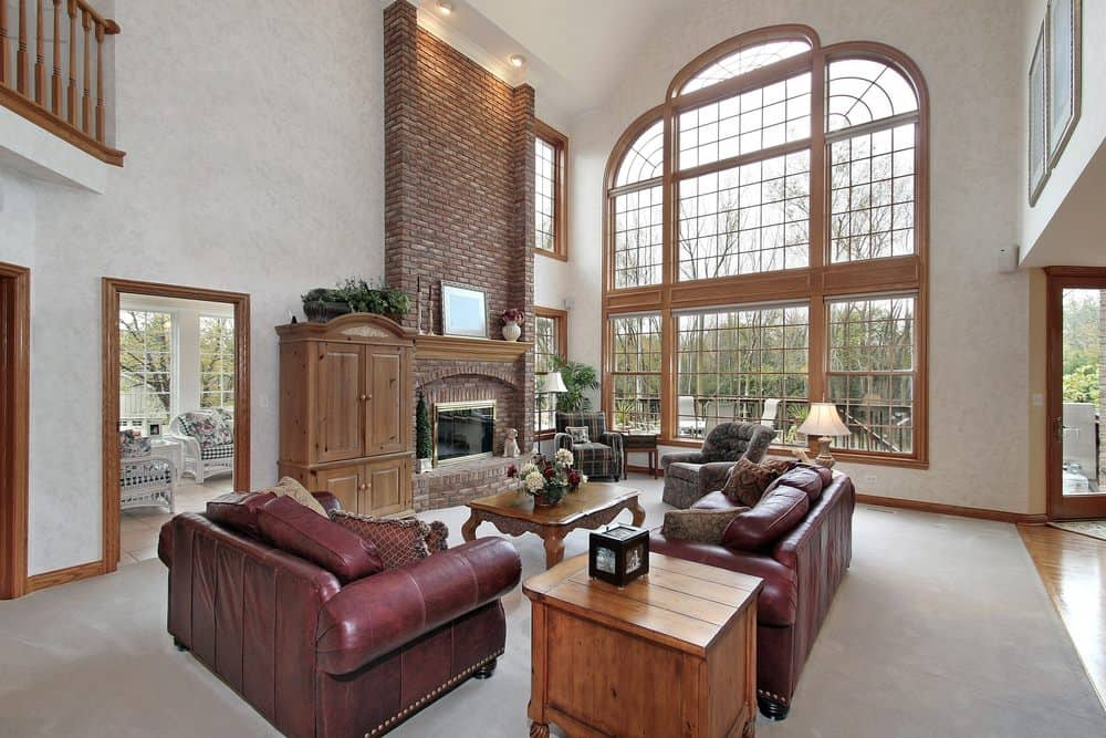 A formal living room featuring a leather sofa set and classy seats along with a brick fireplace, carpet flooring, and white tall ceiling.