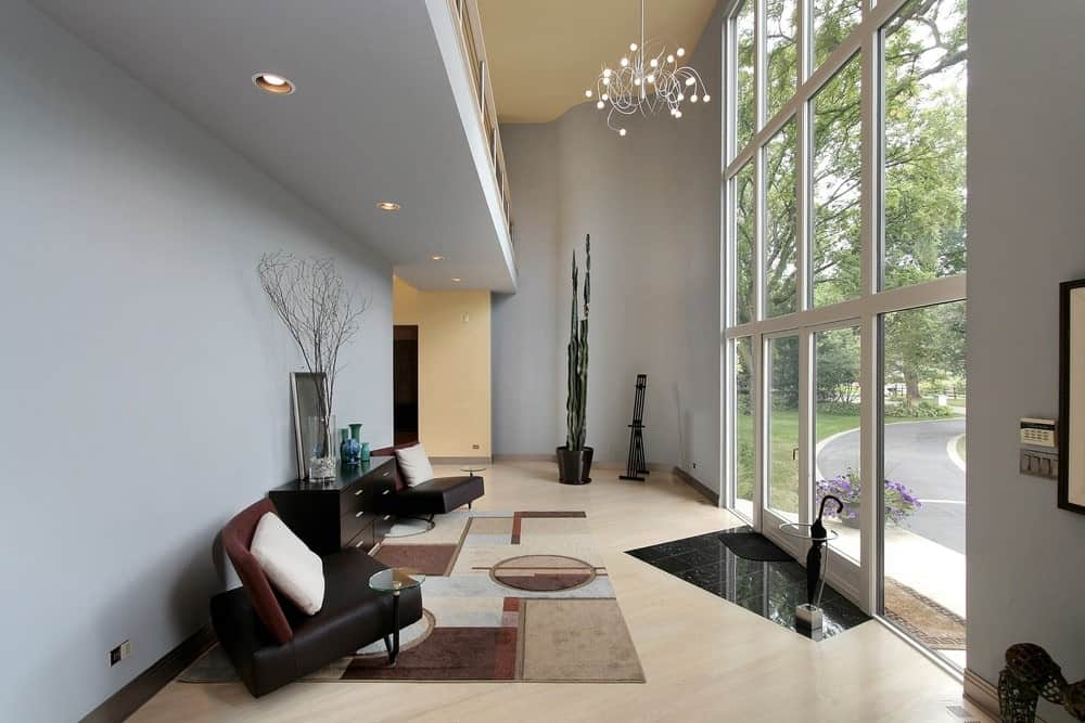 A living space featuring a pair of modish seats and a stylish rug situated just in front of the home's glass door leading to the property's courtyard.