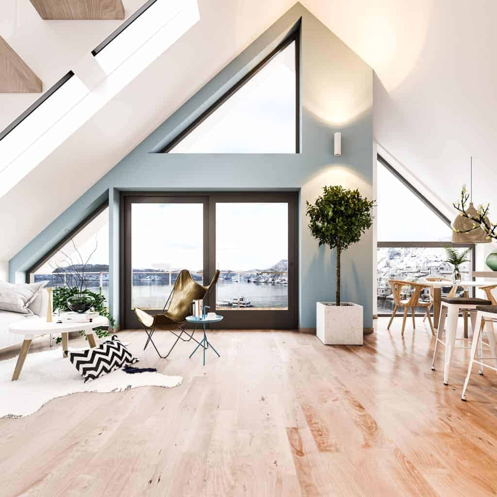 A Scandinavian-Style living space boasting hardwood flooring and a stunning tall ceiling. The home features a gray and white shade for additional style.