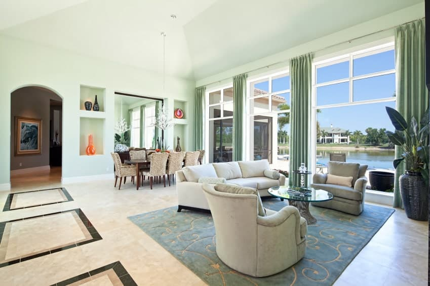 Fresh living space showcasing a stylish flooring topped by a large area rug, mint green walls and a tall ceiling. The area features a comfy set of seats with a glass top center table.