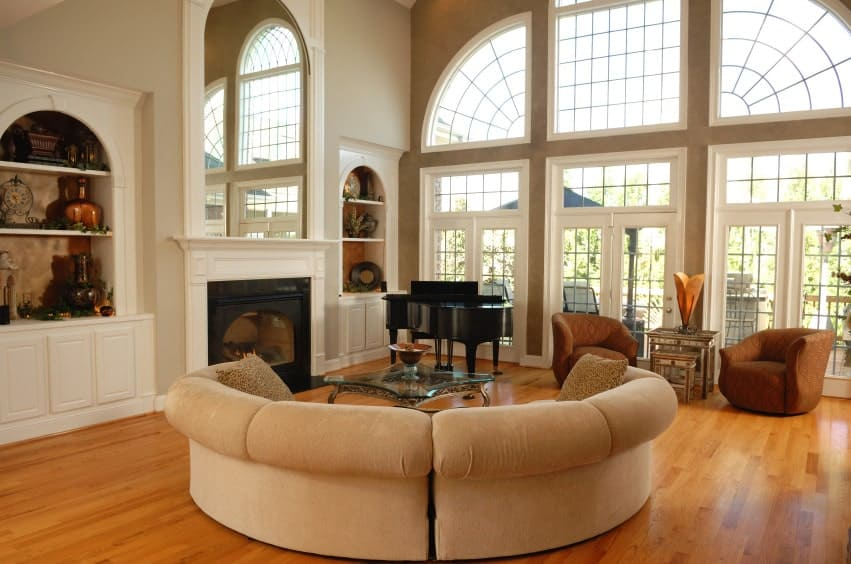 Sophisticated living space with a cozy sofa set, a stylish glass top center table and a fireplace, along with a black piano on the side. It includes rich hardwood flooring and stylish framed windows.