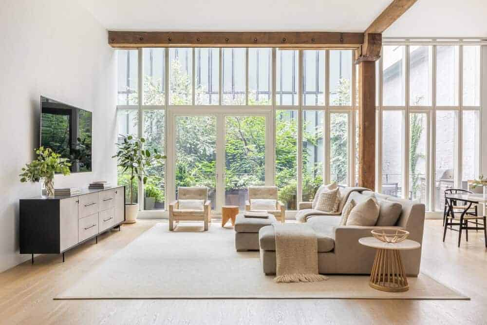 A spacious contemporary living room boasting a modish gray sofa set with a large flat-screen TV on the wall, set in front. The room also offers a large area rug covering the flooring.