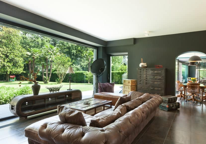 The brown leather sofa set of this living room looks so elegant. Surrounded by the dark-green finish and panoramic windows, the room is astoundingly stylish and stunning.