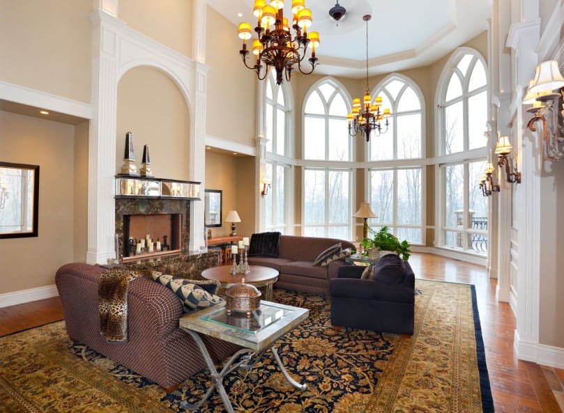 A formal living room boasting classy seats and a vintage rug over the hardwood flooring. The room has a high ceiling and large arched windows that bring natural light in.