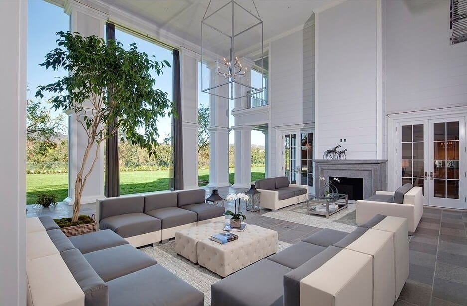 The tall tree placed in the corner helps to balance the height of the space with the low profile of the furniture. Clean lines and geometric shapes counter the contemporary design of the perimeter of the room.