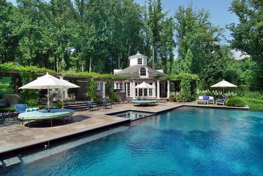 A look at the large swimming pool set in the home's backyard. It has multiple sitting lounges on the side. Images courtesy of Toptenrealestatedeals.com.