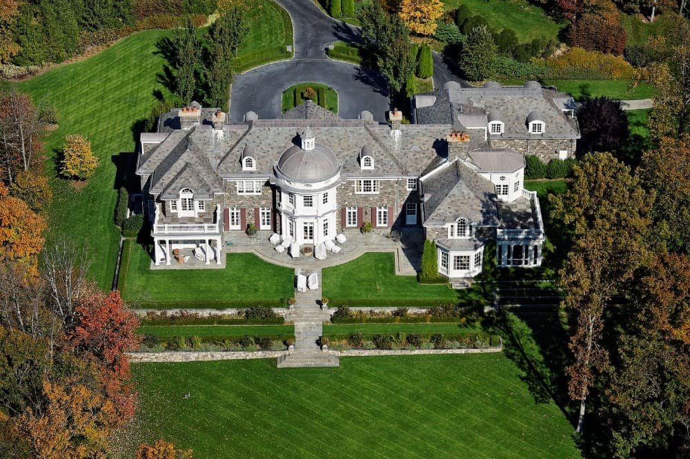 Aerial view of the house boasting its magnificent architecture and its beautiful landscape surrounding the property.