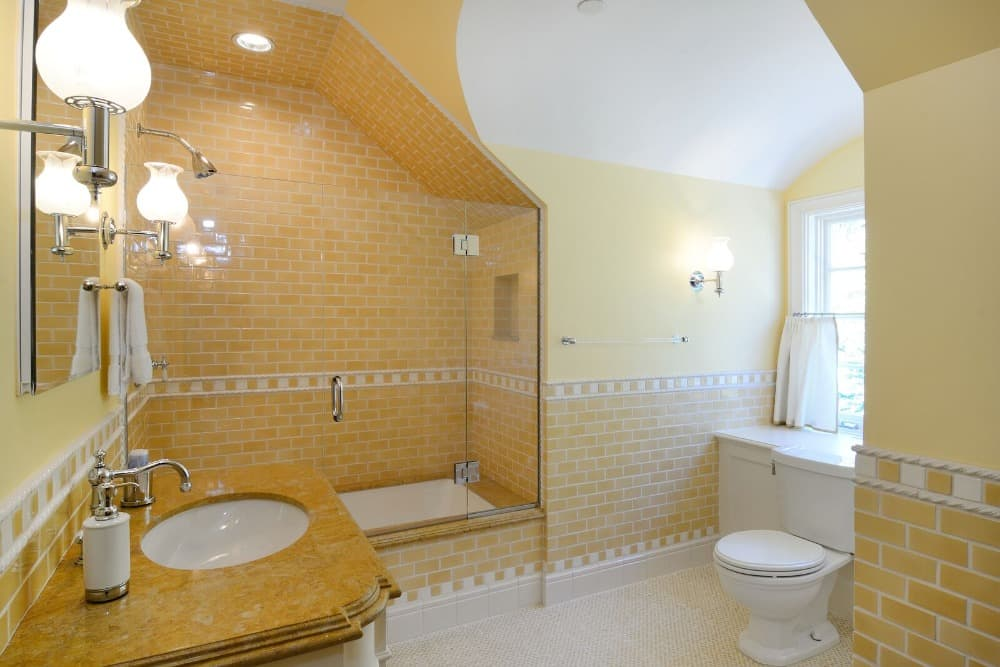 Another one of the bathrooms featuring yellow walls. It has a single sink counter and a bathtub and shower combo. Images courtesy of Toptenrealestatedeals.com.
