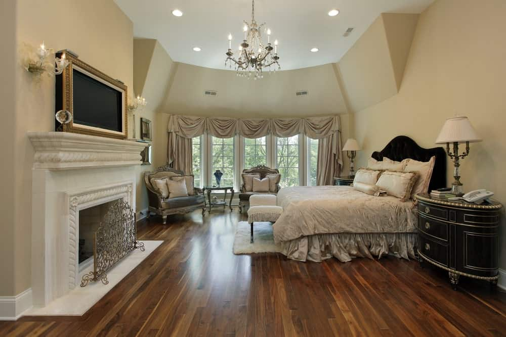 Luxurious master bedroom with lots of lighting, a seating area by the window, and a TV above the fireplace.
