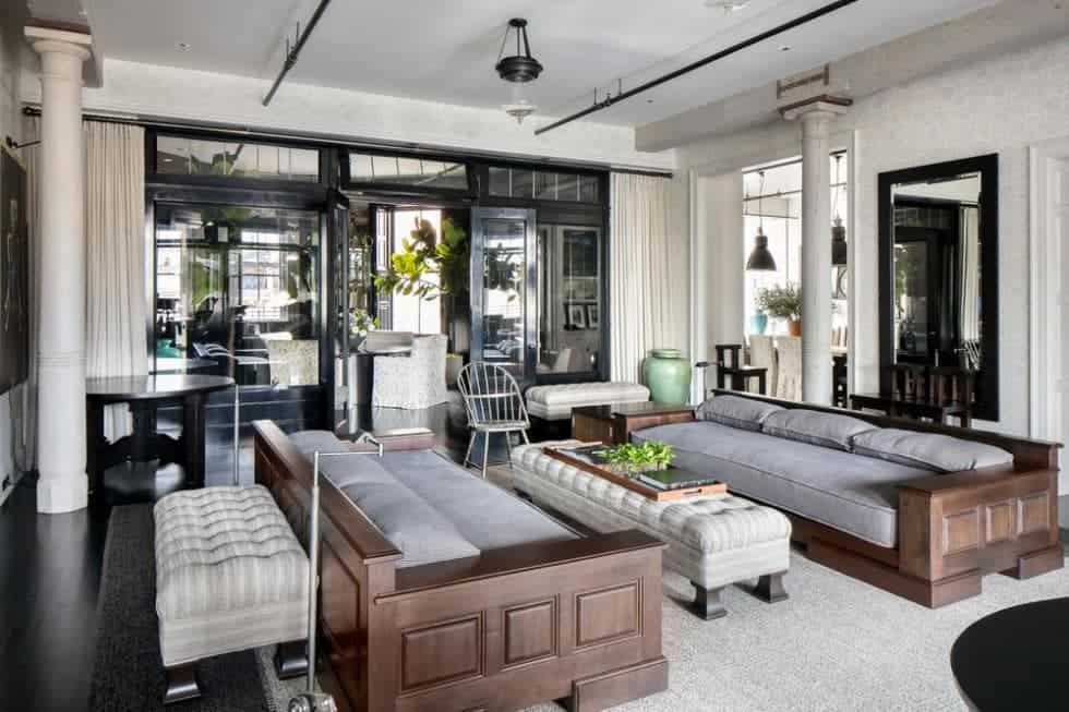 This gorgeous living room has a couple of long wooden sofas fitted with comfortable gray cushions paired with a long cushioned coffee table over an area rug that covers most of the dark wooden flooring.