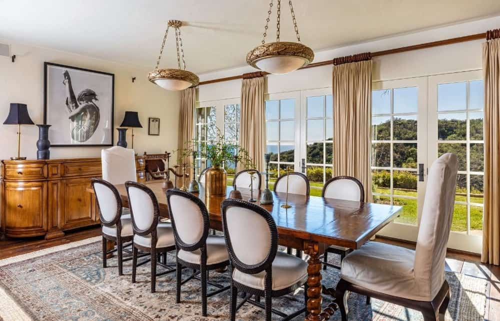 This formal dining room offers a luxurious dining table and chairs set on top of a large area rug lighted by pendant lights. Images courtesy of Toptenrealestatedeals.com.