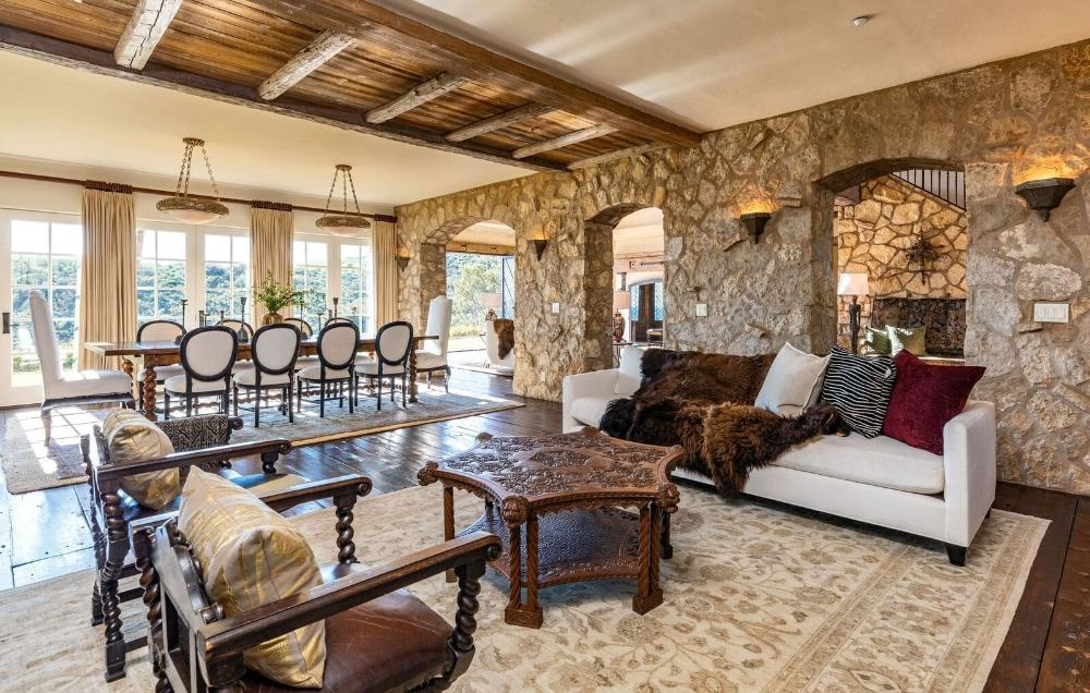 This great room boasts an elegant living space set along with a luxurious dining table set for 10, lighted by wall and pendant lights. Images courtesy of Toptenrealestatedeals.com.