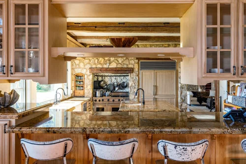 The kitchen offers a breakfast bar counter and a center island with stunning countertops. Images courtesy of Toptenrealestatedeals.com.