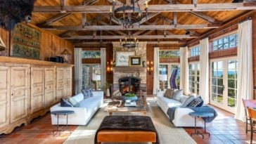 Another one of the home's living spaces. This one is much larger and offers a pair of white couches, along with a stone fireplace. Images courtesy of Toptenrealestatedeals.com.