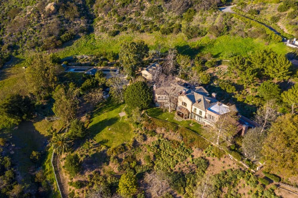 Aerial view of the property and its extent, featuring the lush landscape surrounding it. Images courtesy of Toptenrealestatedeals.com.