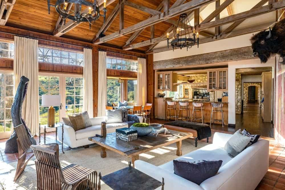 This lviing space features a pair of white couches and a rustic center table, and is set near the breakfast bar area. Images courtesy of Toptenrealestatedeals.com.
