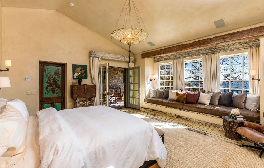 Large bedroom suite with a sunroom area. The room boasts beige walls and a shed ceiling. Images courtesy of Toptenrealestatedeals.com.