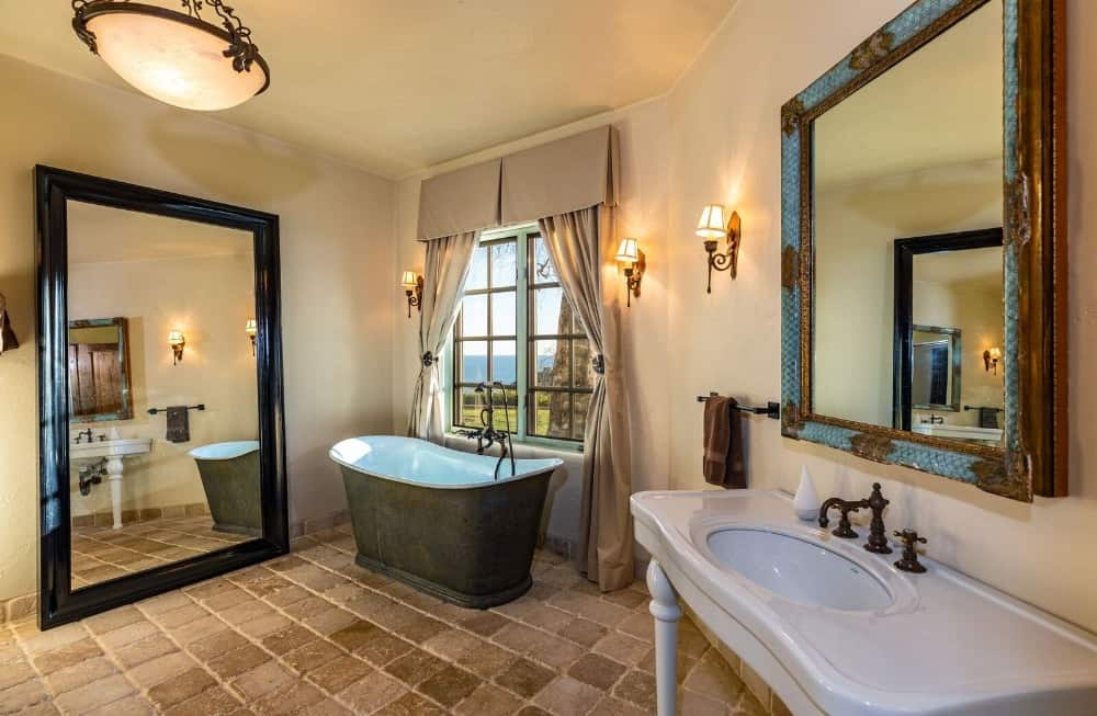 This bathroom features a classy sink counter and a freestanding tub set by the window. Images courtesy of Toptenrealestatedeals.com.