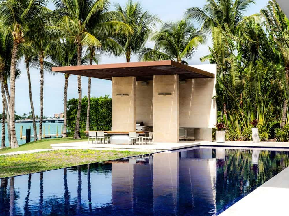 Beside the brilliant swimming of the backyard is an outdoor dining area with an outdoor grilling station all under a large modern structure that has a clear view of the beach through tall tropical trees. Images courtesy of Toptenrealestatedeals.com.