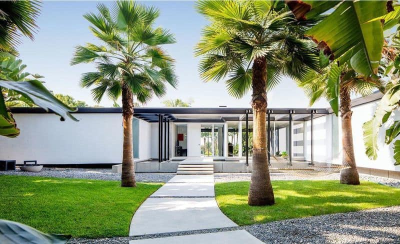 The front walkway of the home has a concrete walkway through a grassy lawn with tall tropical trees giving it a private resort feel. In the distance, the interiors of the house can be seen through mostly glass walls. Images courtesy of Toptenrealestatedeals.com.