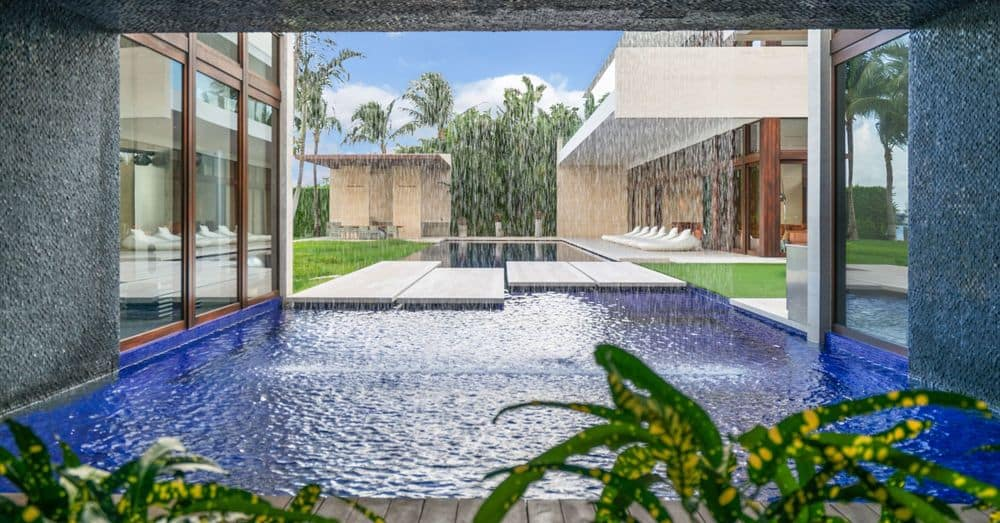 This is part of the lush and luxurious pool of the backyard of the beautiful home. It has an indoor waterfall falling over the extension of the pool bordered by various tropical plants that elevate the tropical escape aesthetic of the house. Images courtesy of Toptenrealestatedeals.com.