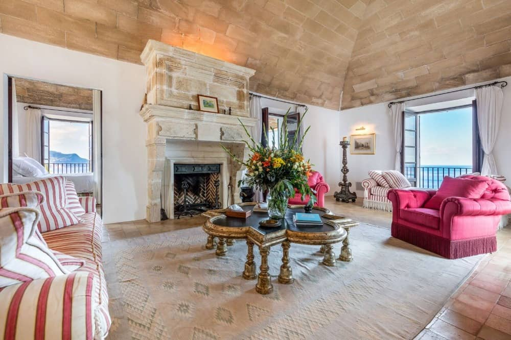 Large formal living room featuring a comfy set of seats and a stylish center island along with a fireplace.