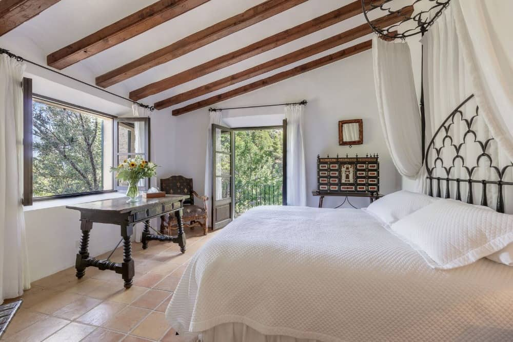 A bedroom featuring tiles beige tiles flooring and white walls, along with a white shed ceiling with wooden beams. It offers a large bed set and a private balcony. Images courtesy of Toptenrealestatedeals.com.