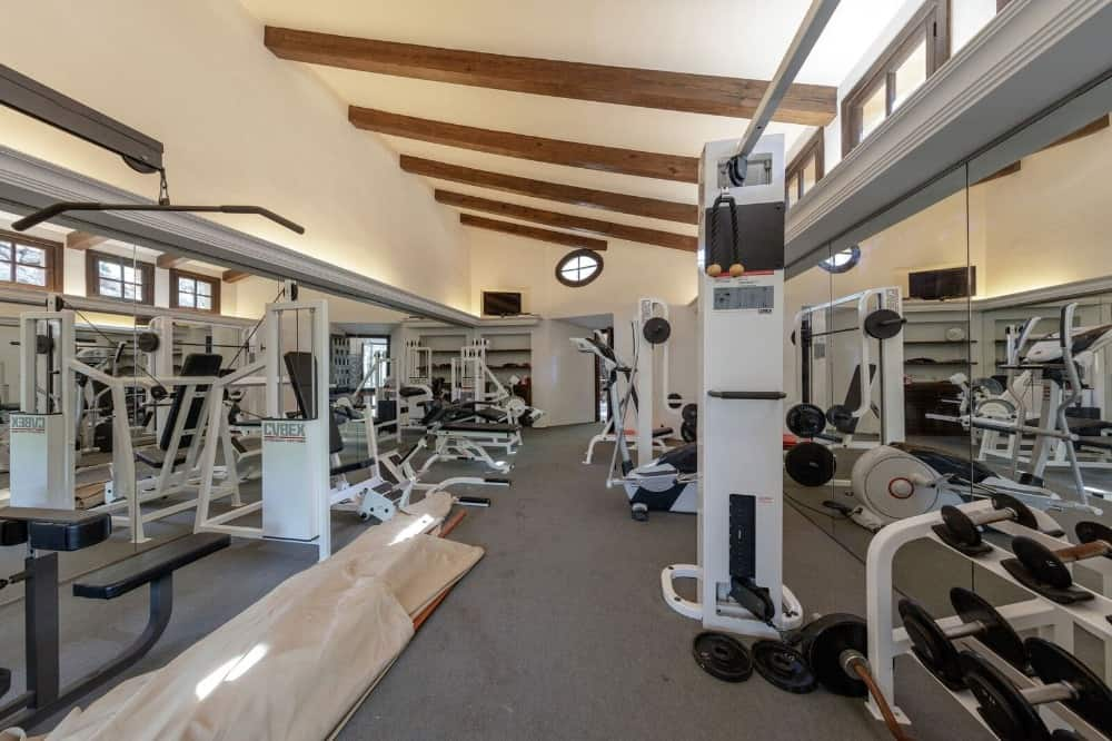 The house also offers a large home gym with white walls and a ceiling with wooden beams. Images courtesy of Toptenrealestatedeals.com.