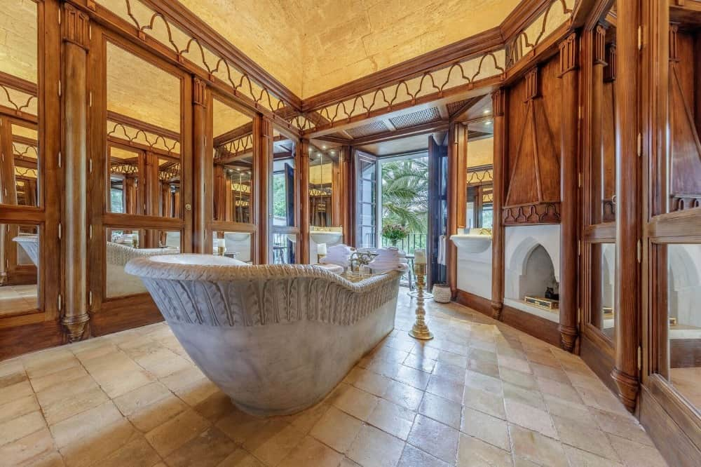 A focused look at this primary bathroom's stunning freestanding tub with a fireplace in the corner. Images courtesy of Toptenrealestatedeals.com.
