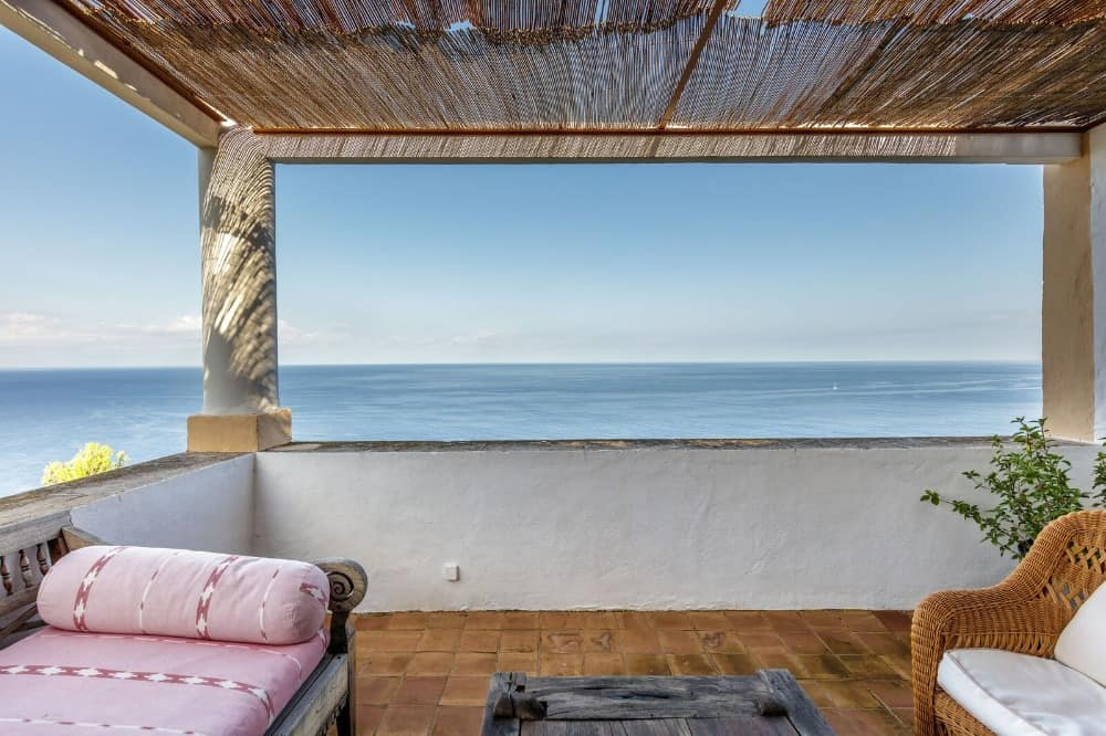 A balcony with a set of seats overlooking the vast ocean view. Images courtesy of Toptenrealestatedeals.com.