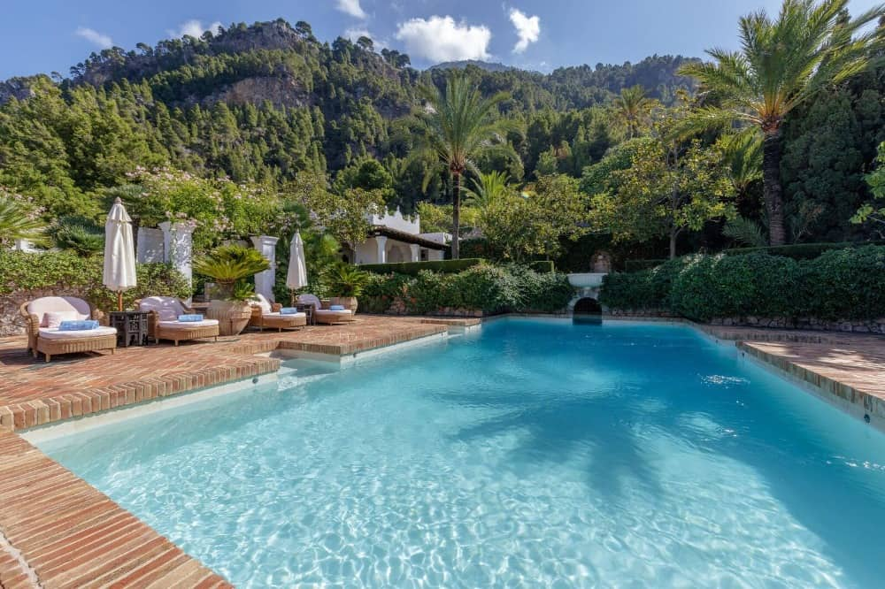 The outdoor swimming pool offers sitting lounges surrounded by the lush greenery of the property. Images courtesy of Toptenrealestatedeals.com.