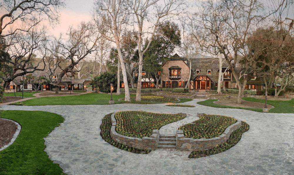A stunning view of the Neverland's wide frontyard featuring its gorgeous garden and walkway.