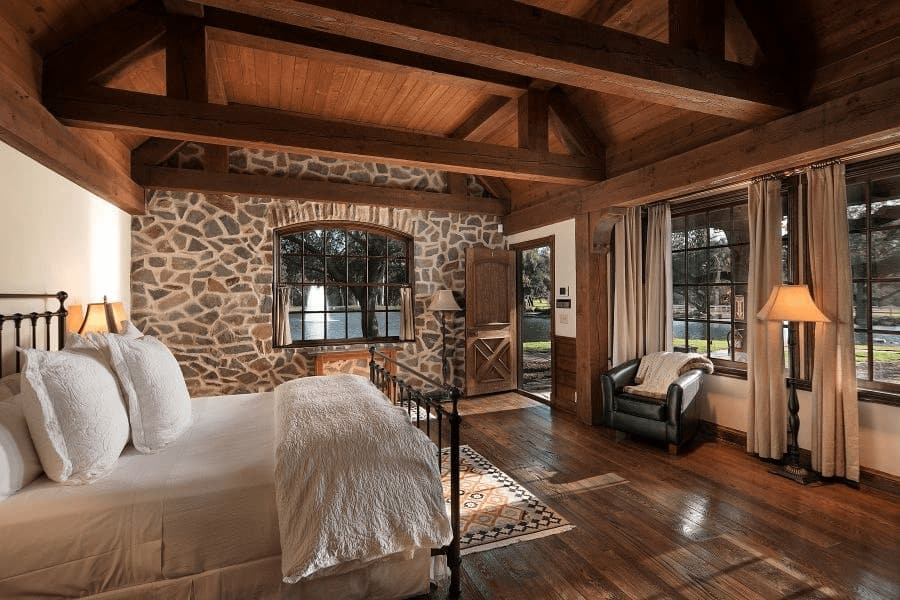 This bedroom suite offers a comfy bed set and a doorway leading to the outdoor area. The room has a stone wall and hardwood flooring. Images courtesy of Toptenrealestatedeals.com.