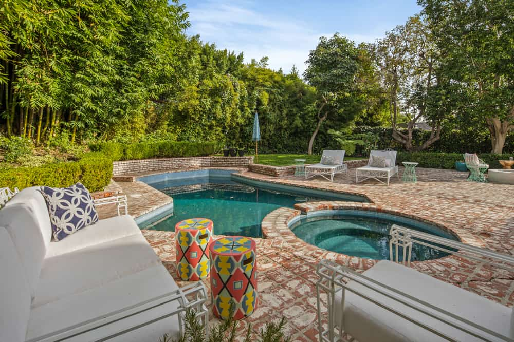 The backyard is surrounded by tall walls of shrubbery and tall trees to provide privacy for those swimming in the charming brick pool. Images courtesy of Toptenrealestatedeals.com.
