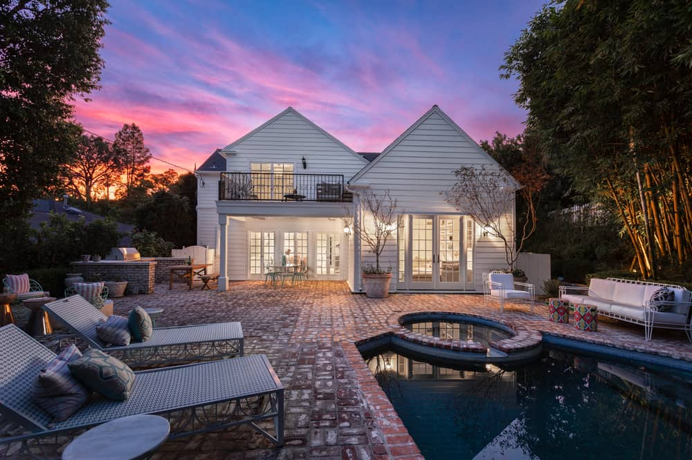 This night time view of the backyard shows the warm yellow glow of the interiors flooding out of the large glass windows and glass doors to pair with the wall-mounted exterior lamps. Images courtesy of Toptenrealestatedeals.com.
