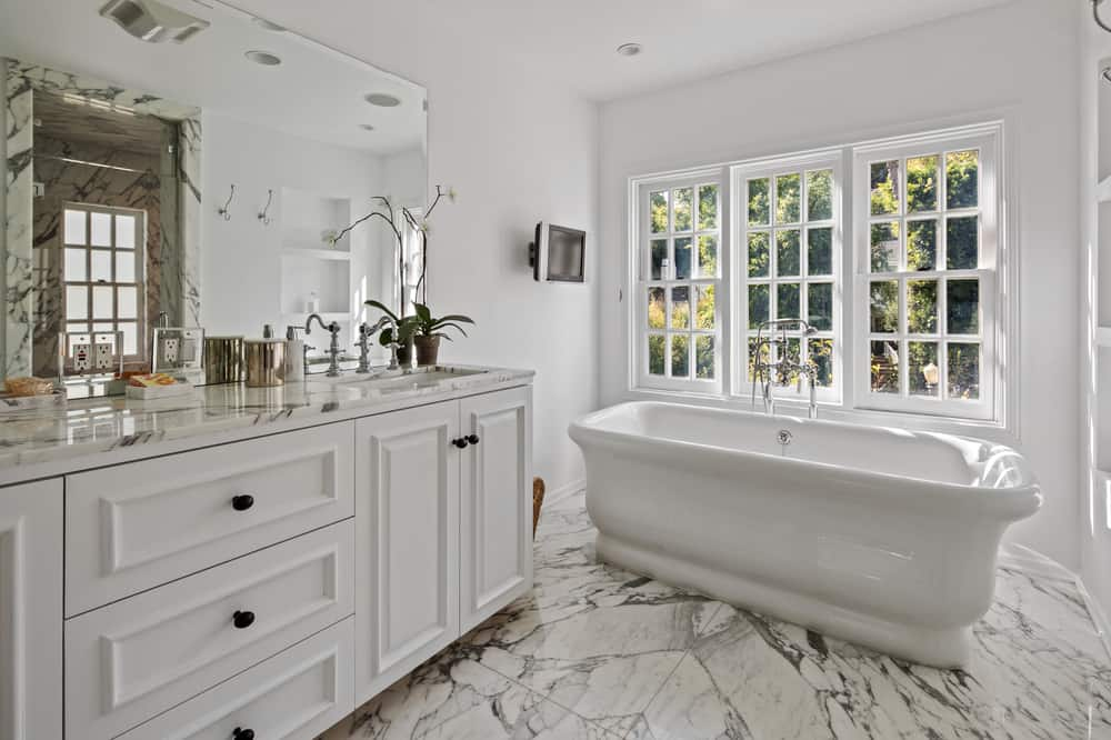 This bathroom has white marbles flooring that matches well with the white freestanding bathtub that is placed by the window beside the white vanity topped with a wall-mounted borderless mirror. Images courtesy of Toptenrealestatedeals.com.